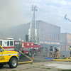 Firefighters battle a blaze in the Rogers Building in the business district of Waterville on Thursday. Photo by John Cross