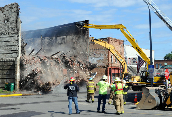 A backhoe pulls down the brick facade of the Rogers building in Waterville after it was gutted by a fire on Thursday morning. Photo by John Cross