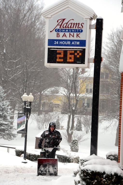 . Dan Juras of Adams Community Bank snowblows the sidewalk in front of the business on Park Street in Adams on Wednesday, Feb. 5, 2014. Gillian Jones/Berkshire Eagle Staff