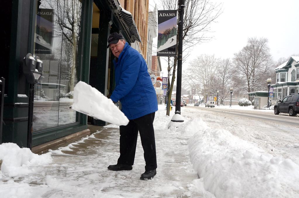 . Bernie Pinsonnault shovels the sidewalk in front of Smith Bros McAndrews Insurance at 45 Park Street in Adams on Wednesday