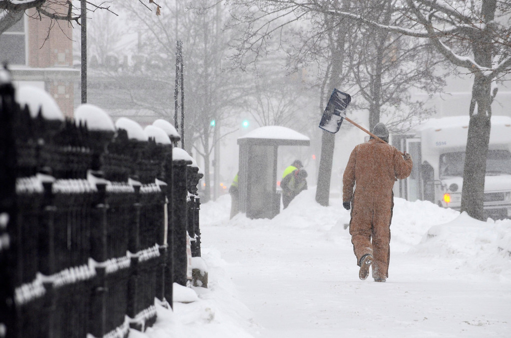. A man walks South on Noprth Street near St. Josephs Church in Pittsfield with a shovel in hand, Wednesday Feb 5, 2014.  Photo by Ben Garver / Berkshire Eagle Staff