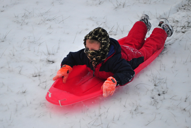 Dominick Pisano, age seven from North Adams, slides down a hill near Greylock Elementary School on fresh snow left by Friday's snow storm.(Jack Guerino/North Adams Transcript)