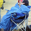 A pair of fans try to stay warm under sleeping bags and hats during the Bethany Lutheran College baseball game against Minnesota-Morris Friday afternoon.