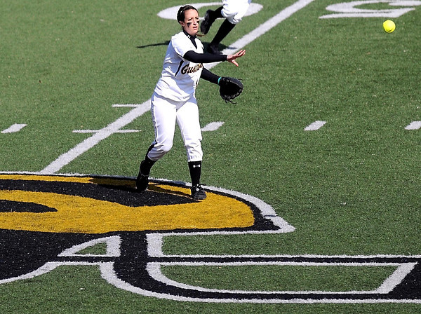 Gustavus Adolphus College second baseman Christina Riester throws to first base from atop the football helmet logo at the center of the school's artificial turf football field during their first home game of the season Thursday.