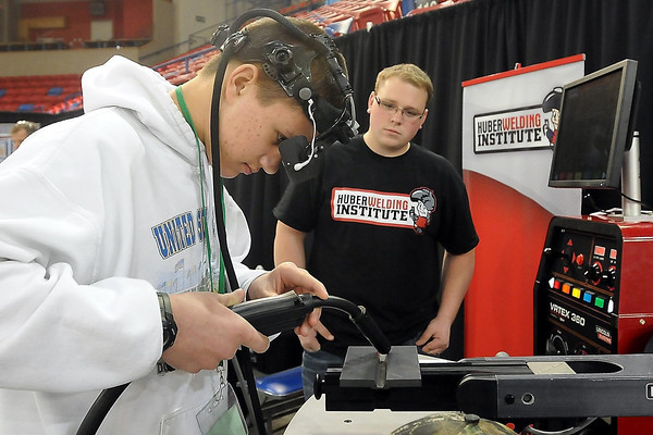 John Cross<br /> United South Central High School student Brian Remington tries his hand at welding on a simulator as Cody Huber of the Huber Welding Institute looks on during a career fair for area high school students Wednesday at the Verizon Wireless Center.