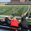 Fans don winter coats and hats as the Gustavus Adolphus College softball team plays its first home game Thursday on the school's artificial turf football field.
