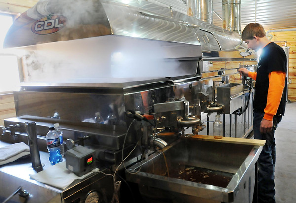 Tanner Hering monitors sap boiling in a stainless steel cooker. Photo by John Cross