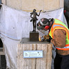 Jerry Olson removes the welds on a sculpture as Eric Harriman and Steve Mork protect the Frandsen Bank building wall Saturday in North Mankato. Photo by Pat Christman