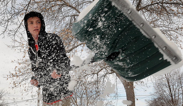 Shawn Asplen tends to the familiar duty of shoveling his sidewalk on Friday after an April snowstorm left several inches of heavy, wet snow across south-central Minnesota. Photo by John Cross