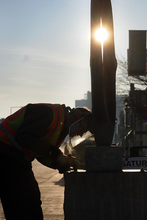 """The City of North Mankato's Jerry Olson removes the welds that hold """"Dances in the Sky"""" to its pedestal in front of Spinner's Bar & Grill in North Mankato Saturday. Photo by Pat Christman"""