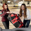 Curling team members Melissa Runing (left) and Caiti Flannery load gear into a van on Tuesday for a trip to Vancouver to compete in an elite curling competition. Photo by John Cross