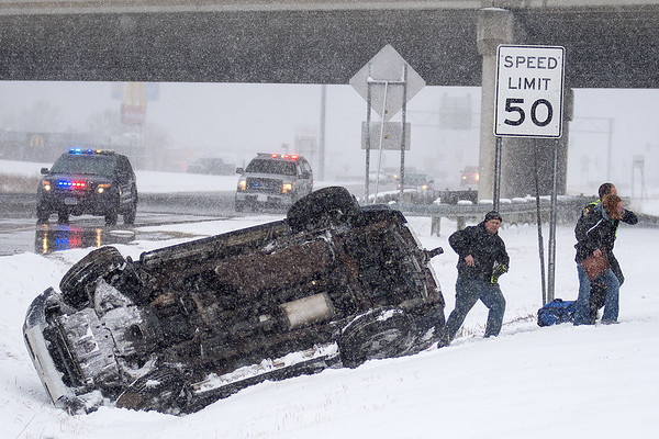 Emergency responders help an occupant of a Toyota 4Runner (right) out of a ditch after the driver of the vehicle flipped the SUV just north of Highway 14 on Highway 169 on Tuesday. No injuries were reported in the single-vehicle accident. Photo by Jackson Forderer