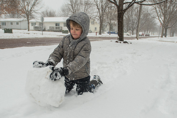 Simon Carlin, 5, makes the beginnings of a snowman near his house in St. Peter on Tuesday. Simon said he was on his spring break from pre-school. The National Weather Service predicted that the region would get three to five inches of snow on Tuesday. Photo by Jackson Forderer