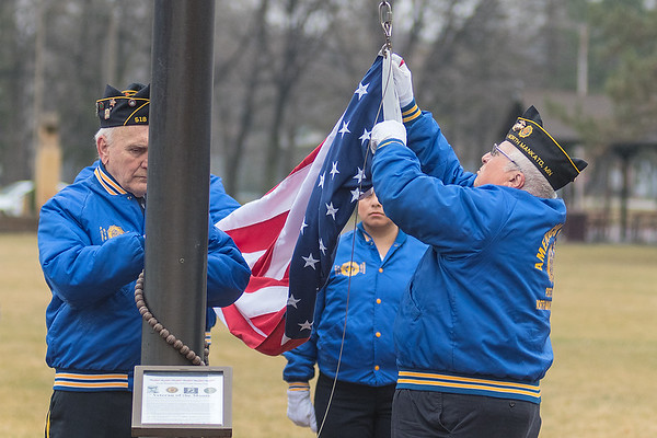 Members of the color guard from the North Mankato American Legion Post 518 take the flag down that was flying for the past month at the Veteran of the Month ceremony in Wheeler Park. Photo by Jackson Forderer