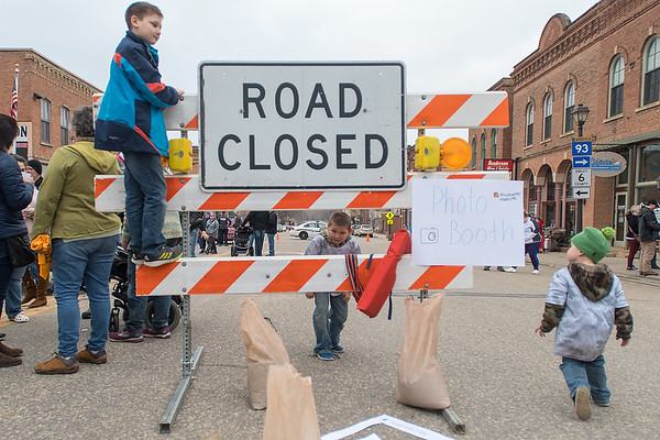 William Menne (left), 9, Elijah Menne, (center), 7, and  Isaac Menne (right), 3, play on a road closed sign on the street in downtown Henderson during Flood Fest on Friday. Photo by Jackson Forderer
