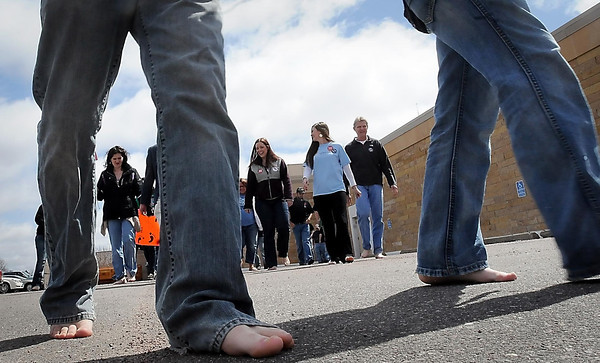 """John Cross<br /> South Central College students step out sans shoes Tuesday as part of a """"One Day Without Shoes."""" Participants in the event designed to show the impact a pair of shoes can make in a person's life received discounts at the SCC bookstore for donating a pair of shoes."""
