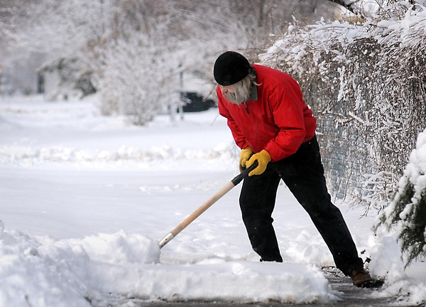 John Cross<br /> Bill Ove of St. Peter leans into a shovel of some of the heavy, wet snow that prompted many area schools to cancel classes on Friday.
