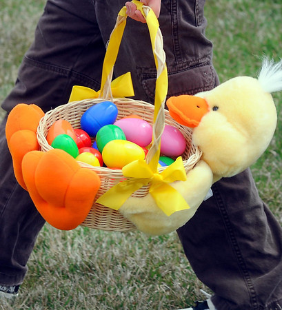 A child with a unique Easter basket carries his recovered eggs back to his parents to be opened Saturday. Photo by Pat Christman