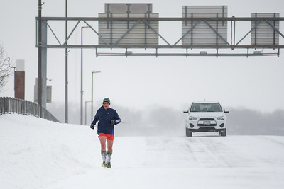Jeff Schultz runs across Veterans Memorial Bridge that connects Mankato and North Mankato on Saturday afternoon. Schultz also stopped to help out a stuck car on a Highway 169 off ramp while running along his route. Photo by Jackson Forderer