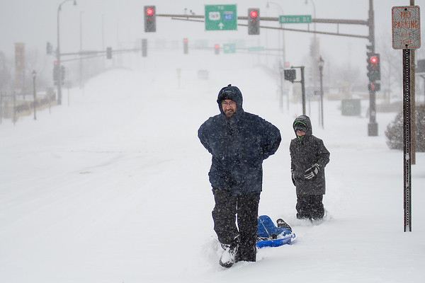 Paul Osterman pulls his son John Osterman, 4, in a sled behind him with James Osterman, 10, following closely behind as they made their way towards Bethany Lutheran College after crossing Veterans Memorial Bridge on Saturday. The National Weather Service reported that Mankato received eight inches of snow as of 4 p.m. Saturday. Photo by Jackson Forderer