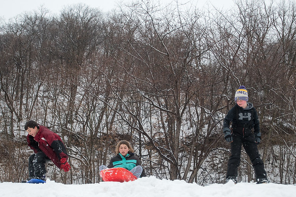 "From left, Michael Barton, 12, Hannah Barton, 12, and Ethan Tauber, 11, get ready to snowboard and sled down a hill at Spring Lake Park one last time Wednesday during what may be the last snowfall of the year. Hannah said about the last snowfall, ""I'm kind of disappointed but I'm kind of happy at the same time,"" and Ethan added, ""I like snow but it should've snowed in December and not in April."" Photo by Jackson Forderer"