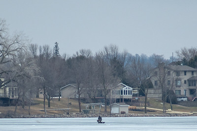 An ice fisherman fishes on Madison Lake on Friday despite signs warning of thin ice. The ice is out longer than normal but is expected to be gone by the fishing opener. Photo by Jackson Forderer