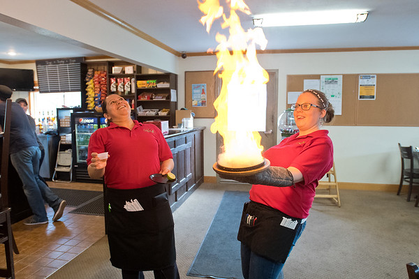 Lucy Osuna (left) and Krystal Hernandez lean back from a flaming appetizer dish at La Plaza Fiesta restaurant on Saturday. Hernandez, the restaurant's owner, said they started serving the dish on Feb. 3, the anniversary of the Madelia fire, to try to make the fire a light subject. Photo by Jackson Forderer