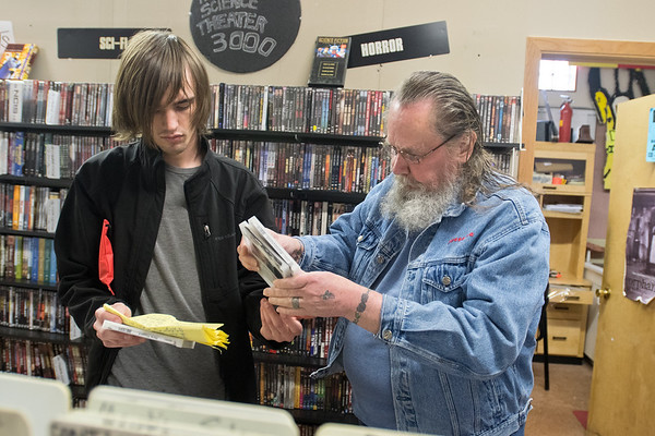 Anthony Powers (left) hands a few Merle Haggard CDs to Dan Rose at Tune Town on Wednesday. The two were checking to see which Haggard albums Rose already owned from a list he wrote down. Tune Town will be participating in Record Store Day 2017. Photo by Jackson Forderer