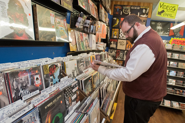 Justin Ellinghysen looks over an album in the vinyl section of Tune Town on Wednesday. Ellinghysen, from Winona, said he comes to Mankato for business but always stops at the music store. Tune Town will be hosting Record Store Day on Saturday from 9 a.m. to 9 p.m. Photo by Jackson Forderer