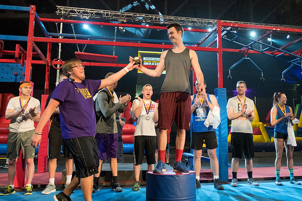 Matt Drosky (center) receives his first place trophy from Dustin Slaughter during the awards ceremony for the Mankato Ninja Warrior competition held on Thursday. Second place went to Moses Wakarura who finished first in the time trials. Photo by Jackson Forderer