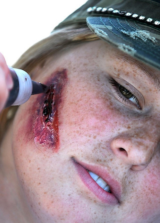 Mount Kato employee Paige Pearson has a wound applied to her face by a makeup artist during Saturday's Zombie Run.