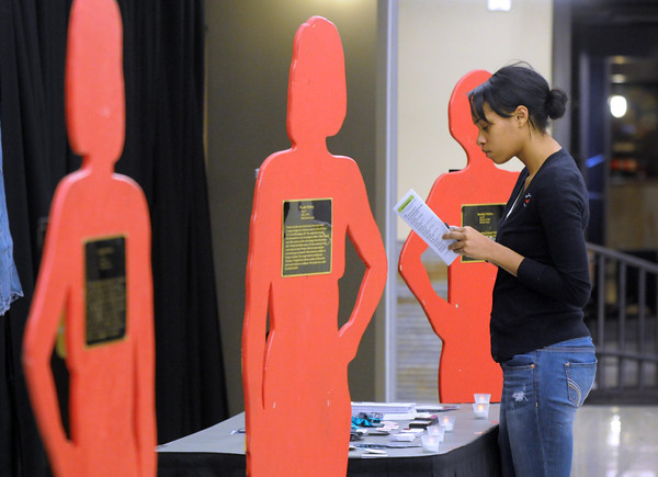Minnesota State University student Bonita Davis reads information about domestic violence near wood cutouts portraying domesic violence victims during a Take Back the Night rally Wednesday at MSU.