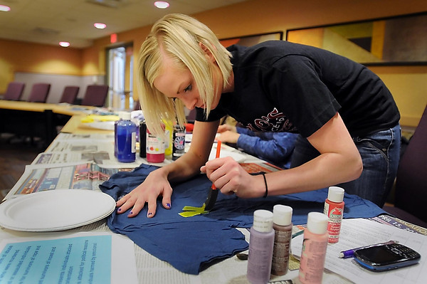 """John Cross<br /> Emily Schrupp, a Minnesota State University senior, decorates a t-shirt on Monday as part of the Clothesline Project. The Clothesline Project addresses the issue of violence against women through the decoration of t-shirts that then will be displayed at MSU and the Coffee Hag as """"the airing of the dirty laundry"""" relating to the issue."""