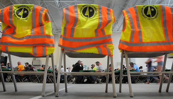 John Cross<br /> Workers attending the Minnesota Department of Transportation's Worker Memorial Day event Monday at the Mankato MnDOT Headquarters maintenance facilty are framed by safety vests representing some of the MnDOT employees who died while working on construction and maintenance projects over the years.