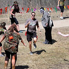 "A runner tries to evade a group of zombies during the Mankato Zombie Run Saturday at Mount Kato. Runners had to complete the course with one flag remaining to ""survive."""