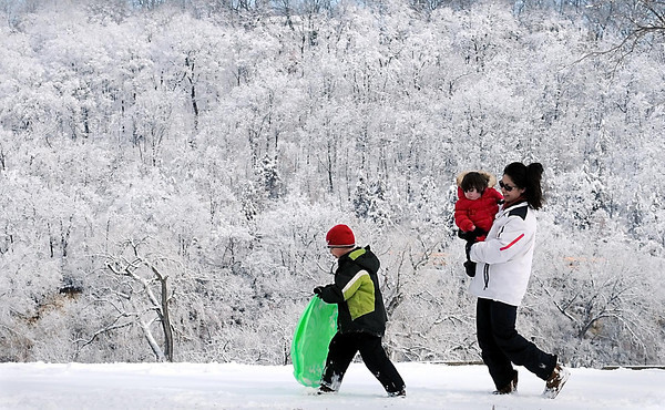 John Cross<br /> Etched against a snow-covered hillside, Isaiah Martinez is trailed by his mother, Benita Martinez and sister, Jasmine, as he heads back to car and off to school Tuesday morning following a few runs down the Sibley Park sliding hill. The 6 inches of snow that fell overnight prompted many area schools including the Mankato Area School Distract to delay classes.