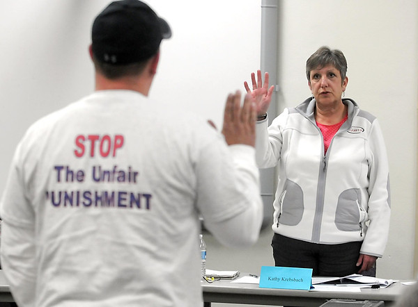 School board chairperson Kathy Krebsbach swears in Rick Drescher, father of USC junior Alyssa Drescher, during an expulsion hearing Thursday at United South Central High School. Photo by Pat Christman
