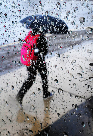 A pedestrian hurries past a rain-streaked bus stop during Monday's rain. Nearly four inches of rain had been reported in some areas with more in the forecast. Photo by John Cross