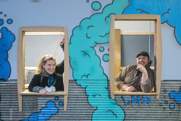Cindy Bourne (left) and Rick Esser (right) pose for a portrait in the windows of a wall that separates the ceramic room from the rest of the shop at Mankato Makerspace. Photo by Jackson Forderer