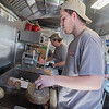 Ben Herzog flips two hamburgers inside The 507 food truck during the first day of business at The Hub in Old Town, Mankato. Steve Wegman (center) said they've had the food truck for about a week and a half. Photo by Jackson Forderer