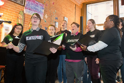 Laura Schultz (second from left) leads the #ICANTKEEPQUIET choir in a song at a Take Back the Night rally held in a packed Coffee Hag on Tuesday. Photo by Jackson Forderer