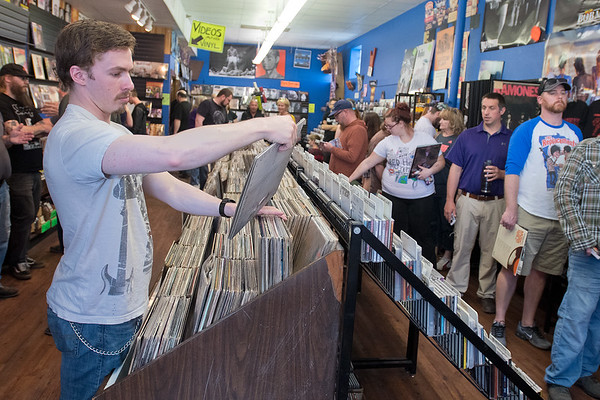 Tony Cordes (left) looks at a record while other customers wait in line at Tune Town on Saturday during Record Store Day, a day observed nationwide at independent record stores. Tune Town owner Carl Nordmeier said that it was like Black Friday for the store, as he saw customers purchase up to $600 worth of vinyl. Photo by Jackson Forderer
