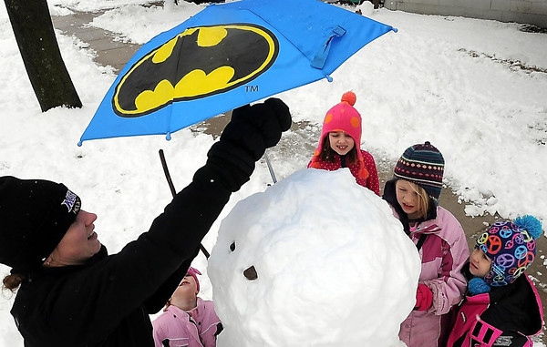 John Cross<br /> Tris Beckendorf adds a spring-like touch to the snowman she and neighborhood kids constructed in the wake of Thursday's snow storm. From left, the children are Keegan Beckendorf, Addey Beckendorf, Grace Guetschow and Lilly Schultz. Beckendorf, a special education teacher at Mankato East High School, had the day off after classes were canceled because of the storm.