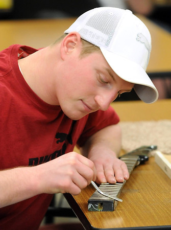 Student Jonny Roemhildt works on the frets of the electric guitar he's making from scratch at SCC.