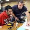 ISouth Central College engineering instructor Jay Stencel helps Javier Rodriguez work on the wiring for an electric guitar.