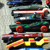 Pinewood derby cars, one complete with a driver, wait their turn to race down the track Saturday.  Photo by Pat Christman