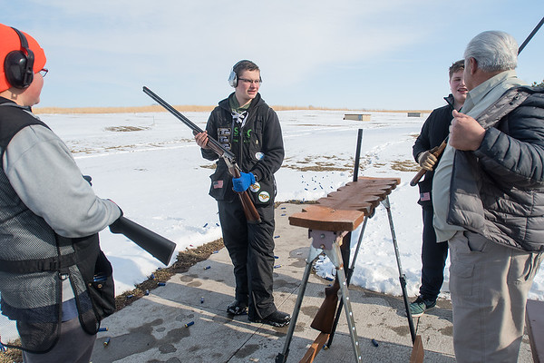 Jackson Gibbs (center) talks with friends and a coach before starting a round of trap shooting at the Caribou Gun Club. Gibbs said he became interested in trap shooting after going out deer hunting with his father. Photo by Jackson Forderer
