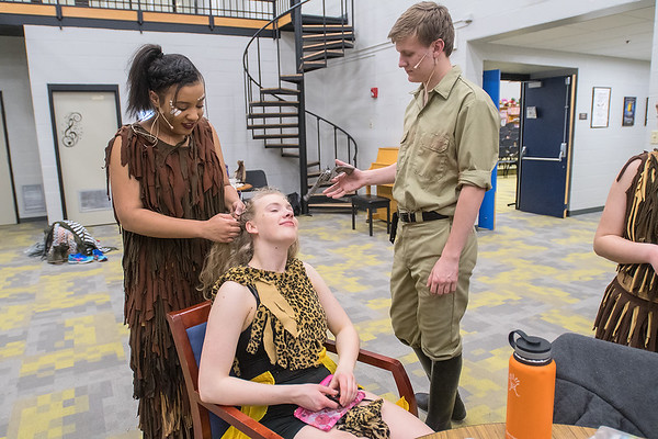Noah Thomas (right) twirls his stage gun as Maya Mukamuri (left) works on Maggie Taylor's hair as the three, all 17 years old, prepared for a dress rehearsal of the play Tarzan at Mankato East on Tuesday. Photo by Jackson Forderer