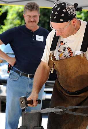 Jim Poling watches as Derrick Phillips of St. Paul forges a knife blade Saturday.