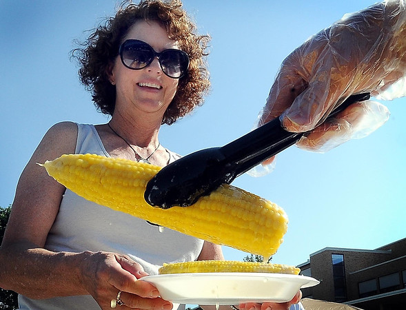 John Cross<br /> Jeanne Steiner is served up a couple of ears of sweet corn slathered in melthing butter at the Y's Club 54th annual Corn Roast on Monday. Money raised from the event is used to fund scholarships for youth YMCA camp.